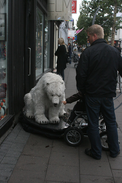 Twins in stroller checking out a bedraggled polar bear.