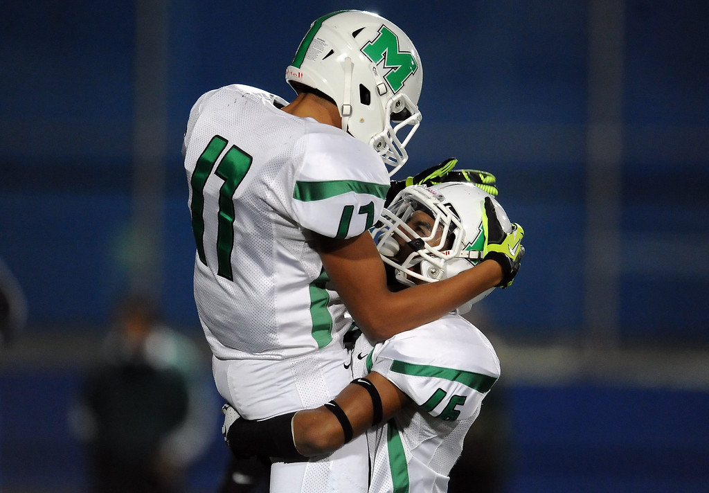 . Monrovia\'s Kahlil Bradley (17) jump into the arms of his teammate Jordan Nathan (16) after catching a pass for a touchdown against San Marino in the first half of a prep football game at Monrovia High School in Monrovia, Calif., on Friday, Nov. 8, 2013.    (Keith Birmingham Pasadena Star-News)