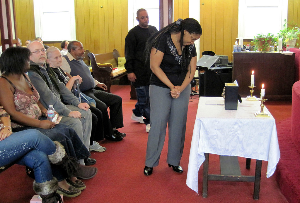 . Nadine Turner looks at a small tribute to the memory of David Glasser in front of the altar at Price Memorial Church in Pittsfield.  Mon Nov 28, 2011 (GARVER)