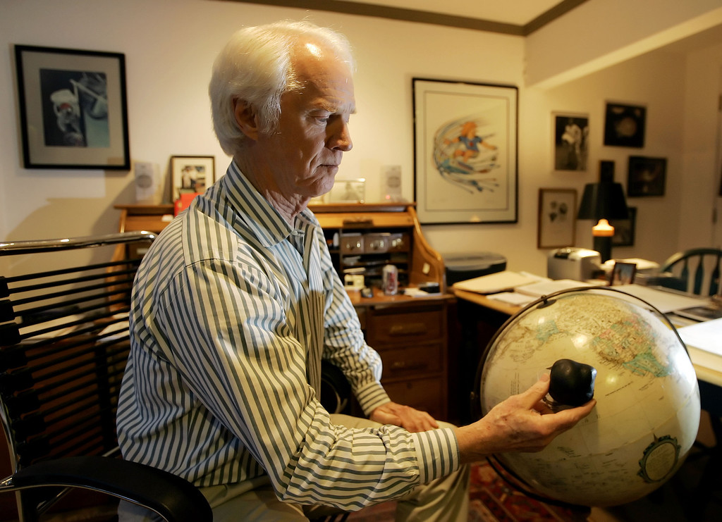 . Former astronaut Rusty Schweickart holds a 3-D model of the asteroid 1998 KY26 near the spot on the globe where an asteroid could hit the earth, during a photo session at his home in Tiburon, Calif., Nov. 1, 2005. Schweickart is currently the chairman of the B612 Foundation. (AP Photo/Eric Risberg)