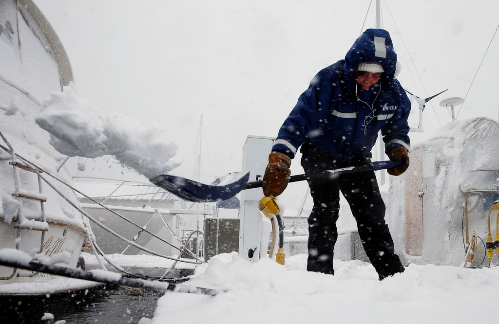 . Gray Harrington clears snow from a dock at the Boston Harbor Shipyard and Marina in Boston, Tuesday, March 13, 2018. Boston finds itself in the bullseye of the third nor\'easter in two weeks, with forecasters warning of up to 18 inches of snow and 2 feet or more to the south. (AP Photo/Michael Dwyer)