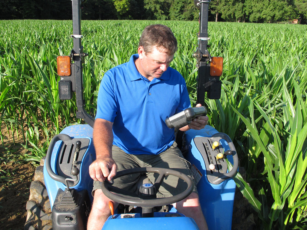 . Timothy Day stops in a Fuquay-Varina, N.C., corn field to check his computer on Saturday, Aug. 24, 2013. The Virginia man travels the country for Maize Quest, using GPS equipment to cut out elaborate mazes for the fall tourist season. (AP Photo/Allen G. Breed)