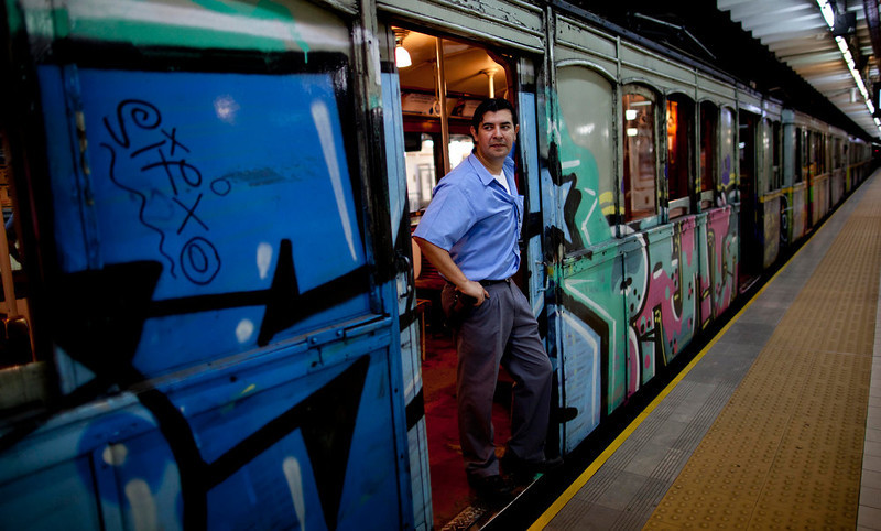 ". A guard stands in the entrance to a wooden carriage car on the historic subway system, Line A, in Buenos Aires, Argentina, Wednesday, Jan. 2, 2013. The city government announced that the almost 100-year-old \'La Brugeoise""wooden carriages will be replaced in a short time by modern Chinese units. (AP Photo/Natacha Pisarenko)"