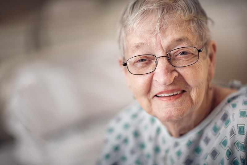 An older woman in a hospital gown smiling.
