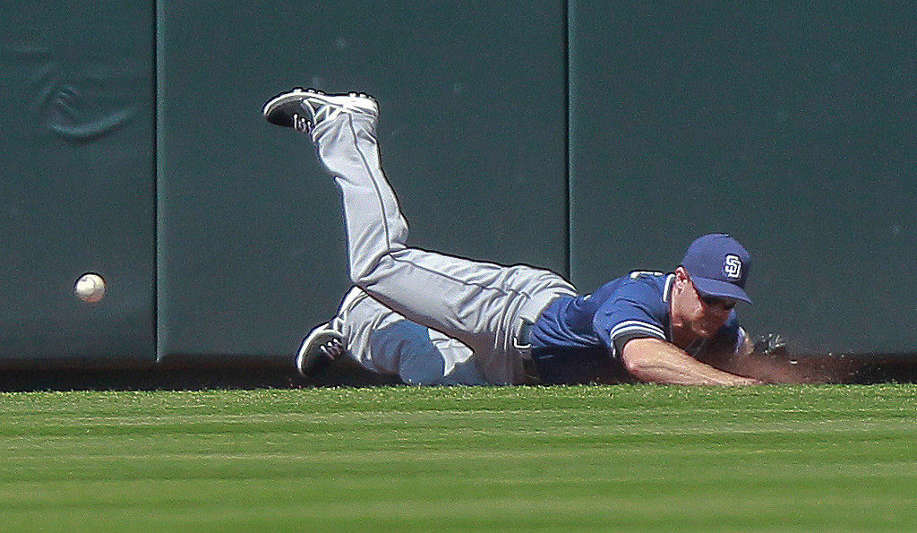 . San Diego Padres\' left fielder Logan Forsythe (11) can\'t hold onto a fly ball at the wall by Colorado Rockies\' Troy Tulowitzki, scoring Corey Dickerson during the first inning of a baseball game Wednesday, Aug. 14, 2013 in Denver. (AP Photo/Barry Gutierrez)