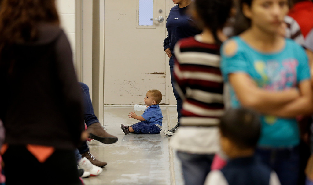 . A toddler sits on the floor with other detainees at a U.S. Customs and Border Protection processing facility, Wednesday, June 18, 2014, in Brownsville,Texas.   (AP Photo/Eric Gay, Pool)