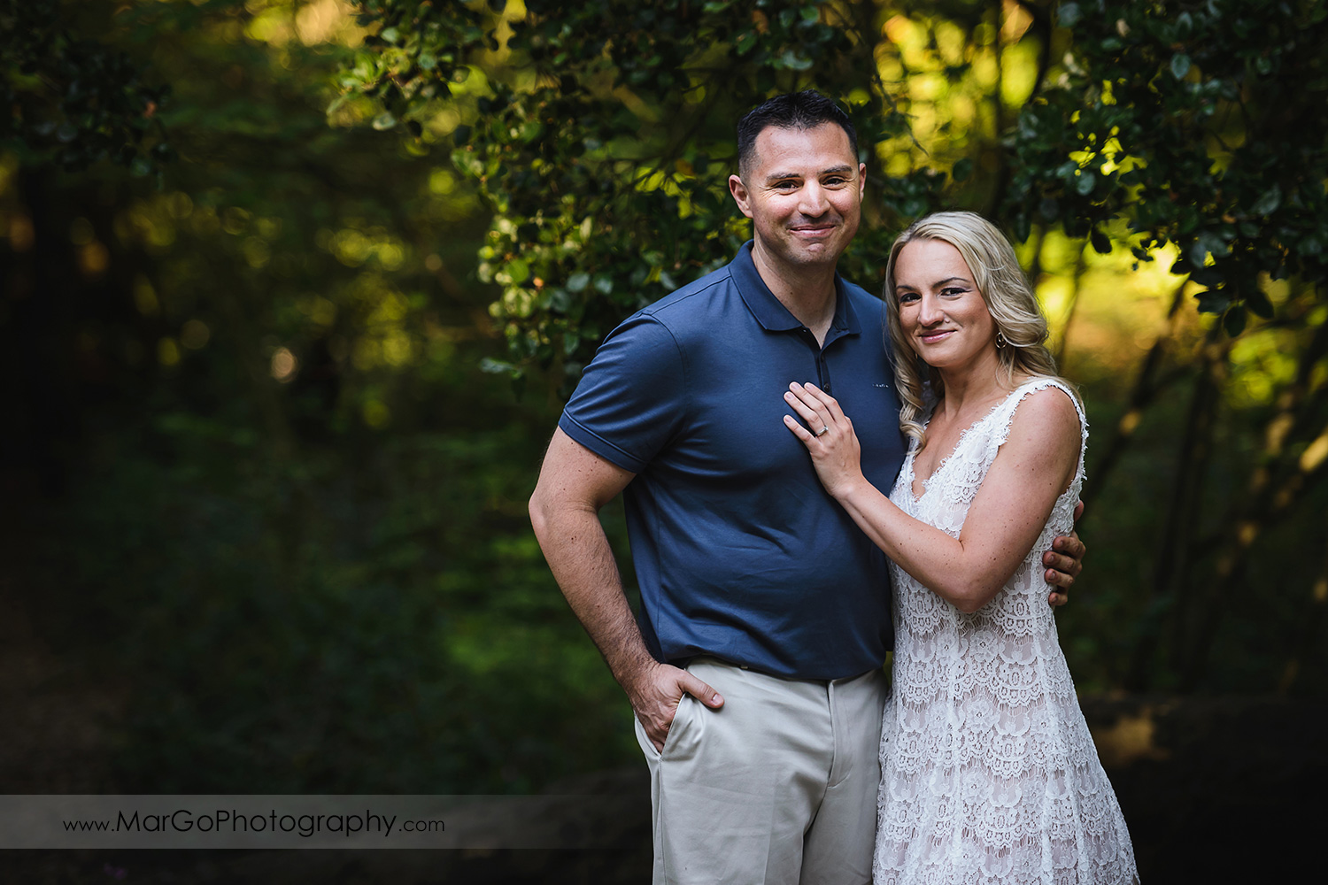 3/4 portrait of man in navy blue shirt and woman in white dress looking into camera during engagement session at San Francisco Golden Gate Park