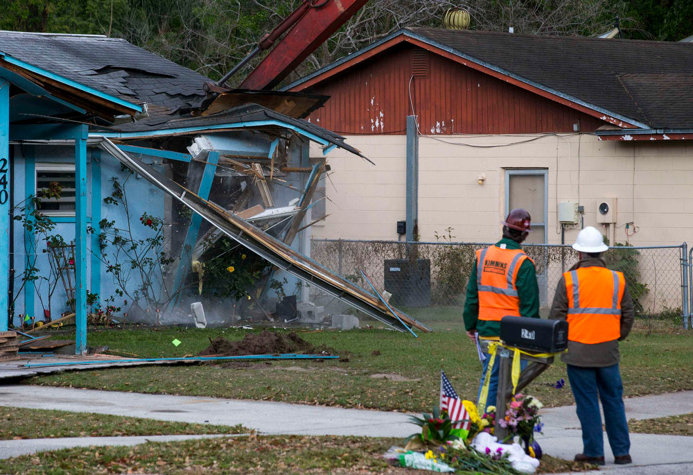 . Demolition crews watch as the house, where Jeffrey Bush was swallowed by a sinkhole, is demolished in Seffner, Florida March 3, 2013. Florida rescue workers ended their efforts on Saturday to recover the body of Jeffrey Bush, who disappeared into the sinkhole that swallowed his bedroom while he slept and demolished the suburban Tampa home due to its dangerous conditions, a rescue spokeswoman said.  REUTERS/Scott Audette