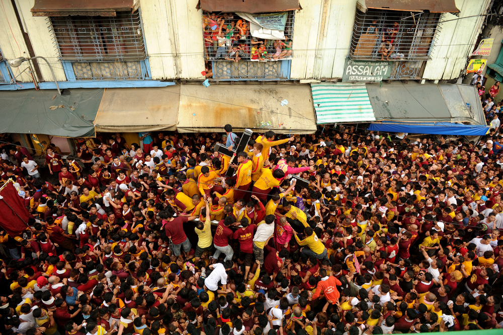 . TOPSHOTS A sea of Catholic devotees jostle for position as they try to touch the life-size statue of the Black Nazarene during the annual procession in honor of the centuries-old icon of Jesus Christ in Manila on January 9, 2013.  Masses of Catholic devotees swept through the Philippine capital on January 9, in a spectacular outpouring of passion for a centuries-old icon of Jesus Christ that many believe can perform miracles.  NOEL CELIS/AFP/Getty Images