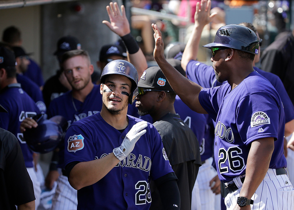 . Colorado Rockies\' Nolan Arenado, center, is congratulated after hitting a 2-run home run against the Milwaukee Brewers during the third inning of a spring training baseball game in Scottsdale, Ariz., Tuesday, March 22, 2016. (AP Photo/Jeff Chiu)