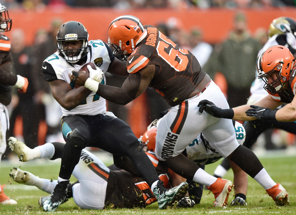 . Jacksonville Jaguars running back Leonard Fournette (27) is stopped by Cleveland Browns defensive tackle Larry Ogunjobi (65) in the first half of an NFL football game, Sunday, Nov. 19, 2017, in Cleveland. (AP Photo/David Richard)