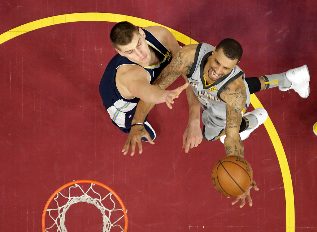 . Cleveland Cavaliers\' George Hill, right, drives to the basket against Denver Nuggets\' Nikola Jokic, from Serbia, in the first half of an NBA basketball game, Saturday, March 3, 2018, in Cleveland. (AP Photo/Tony Dejak)