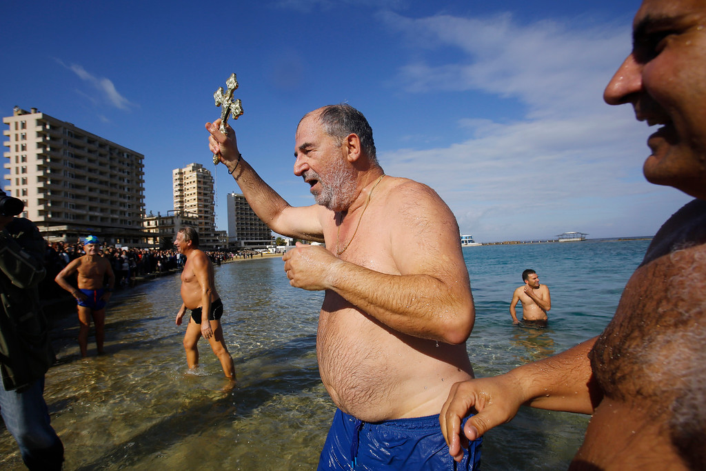 . A swimmer holds thecross after it was thrown from an Orthodox priest into the water, during an epiphany ceremony to bless the sea waters at Famagousta or Varosia beach with the abandon hotels, are seen in the background, in the Turkish Cypriots breakaway north part of the divided island of Cyprus, Wednesday, Jan 6, 2016. More than 1,000 Orthodox Christian faithful attended the  Epiphany Day blessing of the waters in Famagusta in Cyprus�, the first time the ceremony has taken place since 1974 when the small island nation was cleaved along ethnic lines. (AP Photo/Petros Karadjias)