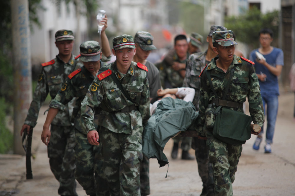 . Armed police rescue the wounded after a 6.5-magnitude earthquake on August 3, 2014 in Zhaotong, Yunnan province of China. A 6.5-magnitude earthquake hit Zhaotong\'s Ludian county at a depth of 12 kilometers. The quake struck Longtoushan Township at 4:30 pm, Beijing time on Sunday, about 50 kilometers from the city center of Zhaotong. (Photo by ChinaFotoPress/Getty Images)