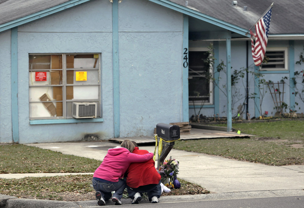 . Jeremy Bush, right, is consoled by an unidentified woman Sunday, March 3, 2013, as he sits outside a home where a sinkhole opened up underneath a bedroom late Thursday evening, swallowing his brother, Jeffrey Bush, in Seffner, Fla. Crews on Sunday began the demolition of the Florida home.  (AP Photo/Chris O\'Meara)