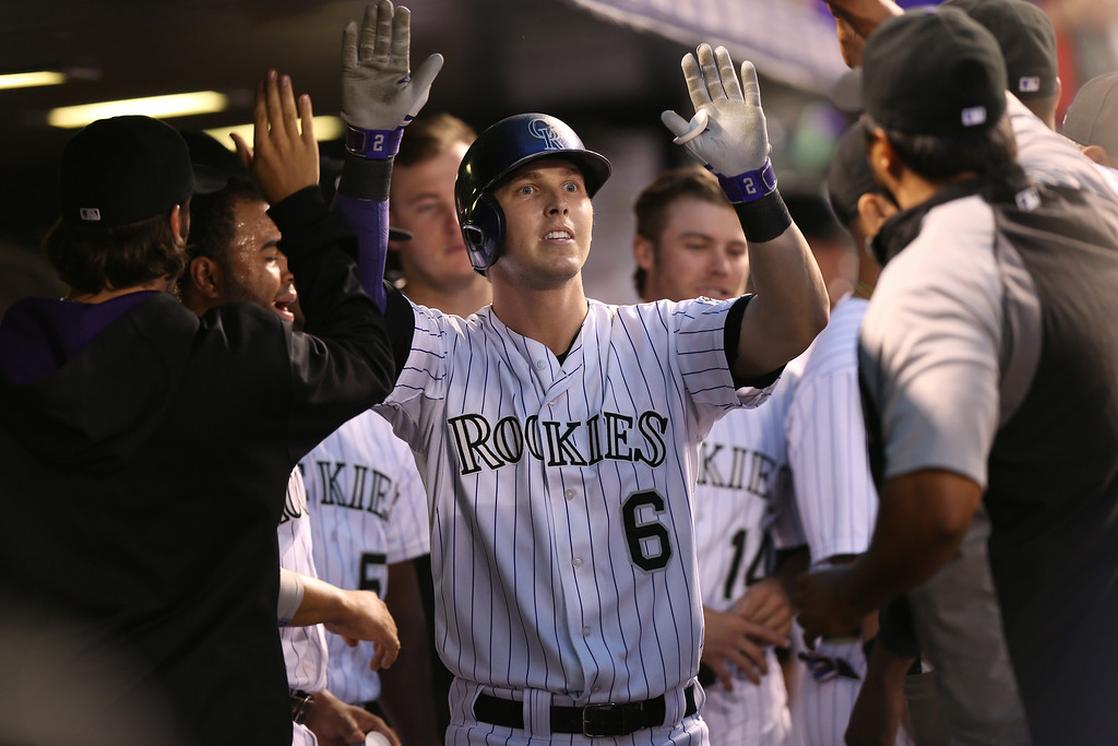 . Colorado Rockies\' Corey Dickerson, center, is congratulated by teammates after hitting solo home run against the Pittsburgh Pirates in the seventh inning of their 8-1 victory in a baseball game in Denver, Saturday, July 26, 2014. (AP Photo/David Zalubowski)