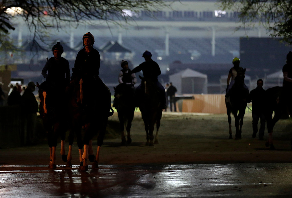 . Horses leave the track after an early morning workout at Churchill Downs Wednesday, May 1, 2013, in Louisville, Ky. (AP Photo/Charlie Riedel)