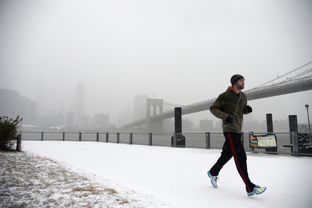 . A man runs in the snow along the East River in Brooklyn Bridge Park, New York, USA, 21 January 2014. Snow and sub-zero temperatures continue to be forecast in the region, according to weather reports.  EPA/ANDREW GOMBERT