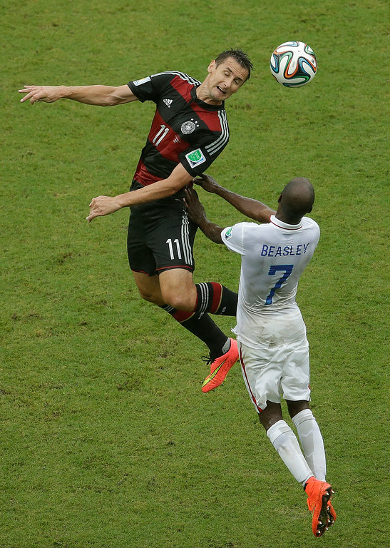 . Germany\'s Miroslav Klose and United States\' DaMarcus Beasley (7) go up for a header during the group G World Cup soccer match between the USA and Germany at the Arena Pernambuco in Recife, Brazil, Thursday, June 26, 2014. (AP Photo/Hassan Ammar)
