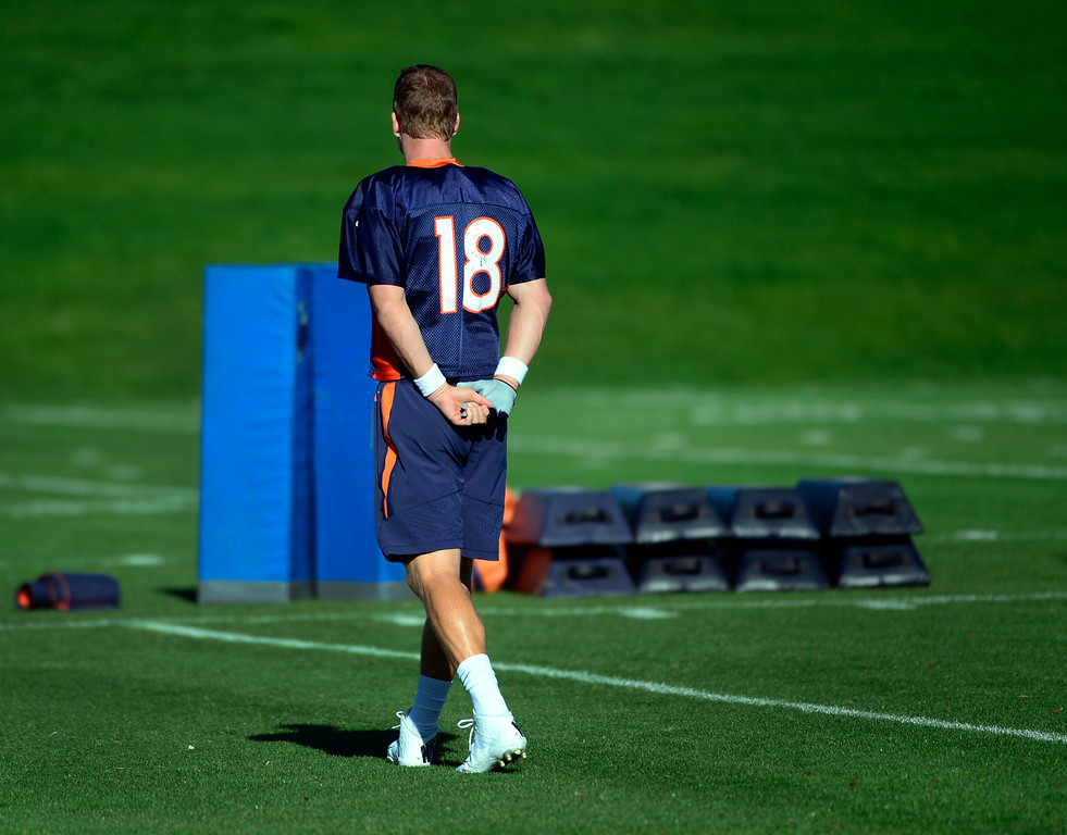 . Quarterback Peyton Manning spends a short time alone before the start of practice. The Denver Broncos football team gets in their final day of practice during training camp at Dove Valley on Friday, Aug. 15, 2014. (Photo by Kathryn Scott Osler/The Denver Post)
