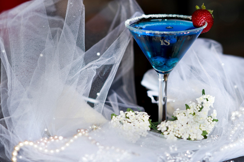 """The Bride  - """"Bride IS""""  1.5 oz. ISVodka  1 oz Blueberry Schnapps  .5 oz Blue Curacao 3 Blueberries 1 Strawberry  Add ISVodka, Blueberry Schnapps and Blue Curacao to ice-filled shaker... shake well.  Rim a martini glass with sugar.  Now pour.  Add blueberries and strawberry.  Photograph by Mark Bowers. Set-up and props by Kiki Kalor."""