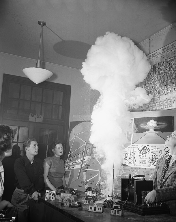 . Students set off a simulated atomic bomb explosion during classroom study of atomic energy at Anacostia High School in Washington D.C., March 25, 1950. The explosion was made by igniting a mixture of Sulfur and Zinc with a high frequency spark and the model houses are used to compare the size of the smoke cloud. The students are, left to right: Charles Jones, Joan Collinge and Charles Williams. (AP Photo/Henry Burroughs)