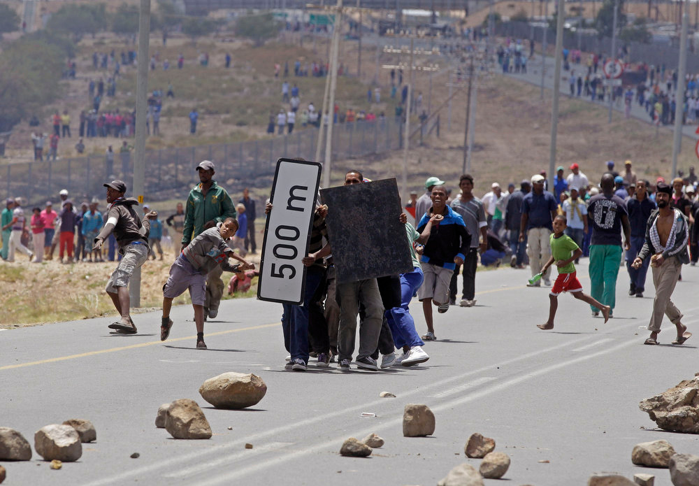 Description of . Striking farm workers throw rocks at South African police as they  demonstrate in De Doorns , South Africa, Thursday, Jan 10, 2013. Striking farm workers in South Africa have clashed with police for a second day during protests for higher wages. The South African Press Association says police on Thursday fired rubber bullets at rock-throwing demonstrators in the town of De Doorns in Western Cape province, and protests were occurring in at least two other towns. (AP Photo/Schalk van Zuydam)