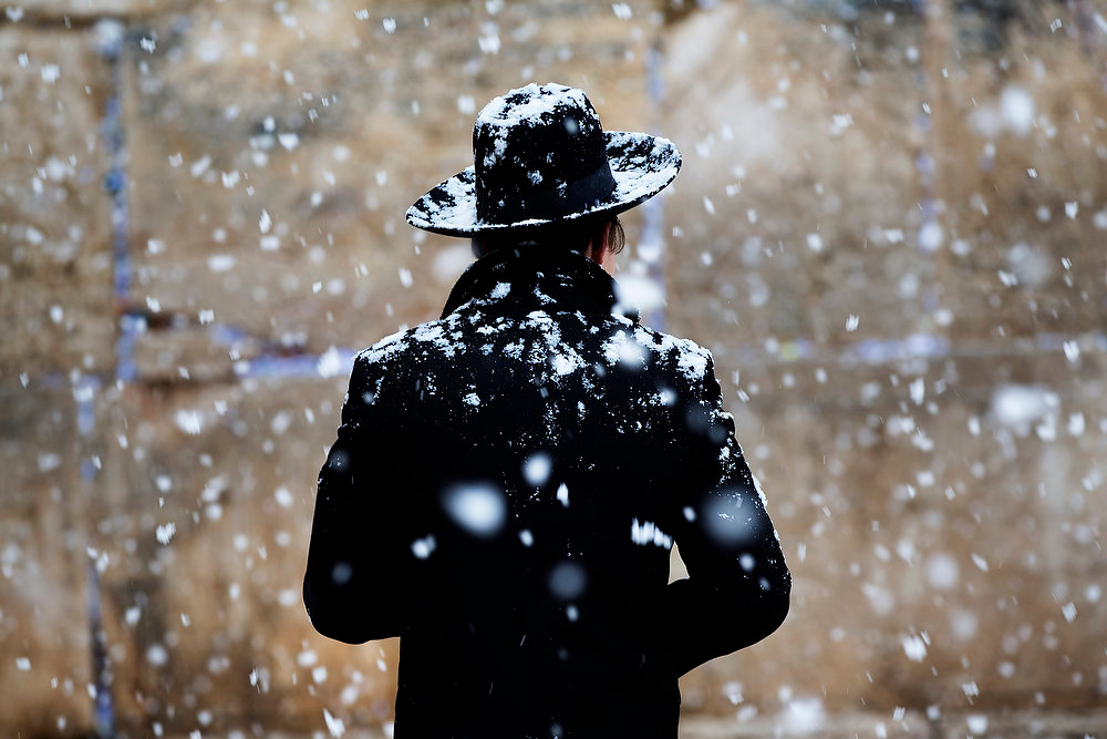 . Snow falls as an ultra-orthodox Jewish man walks at the Western Wall in Jerusalem\'s Old City, Thursday, Jan. 10, 2013. Stormy weather conditions continued on Thursday with snow, torrential rains and strong winds across the region. (AP Photo/Bernat Armangue)