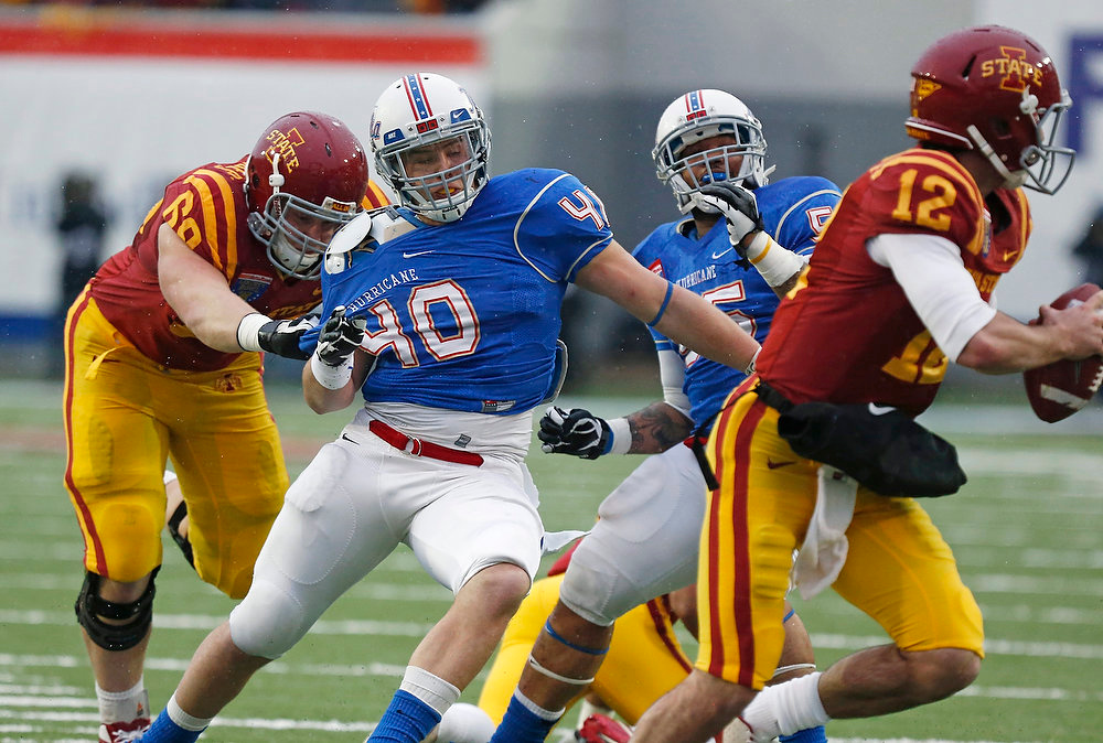 . Tulsa linebacker Trent Martin (40) is tied up by Iowa State offensive linesman Kyle Lichtenberg (69) as he pursues Iowa State quarterback Sam B. Richardson (12) in the second quarter of the Liberty Bowl NCAA college football game in Memphis, Tenn., Monday, Dec. 31, 2012. (AP Photo/Rogelio V. Solis)