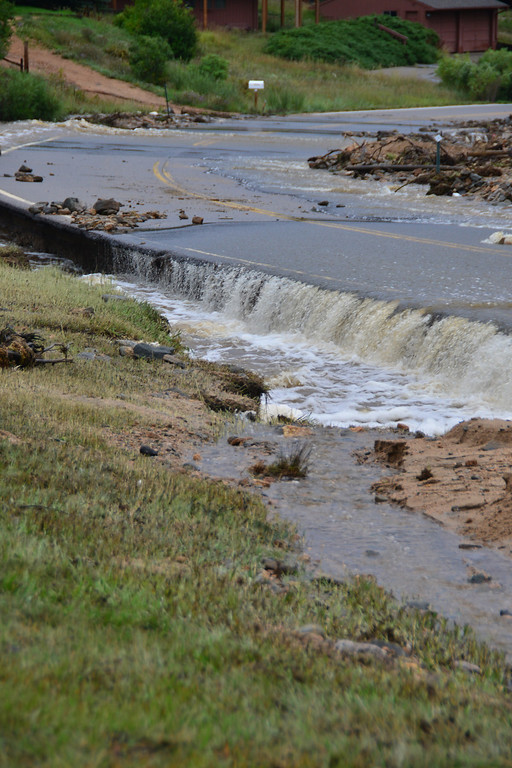 . Floodwater from Fish Creek has undercut the pavement of Fish Creek Road. John Cordsen/Estes Park Trail-Gazette