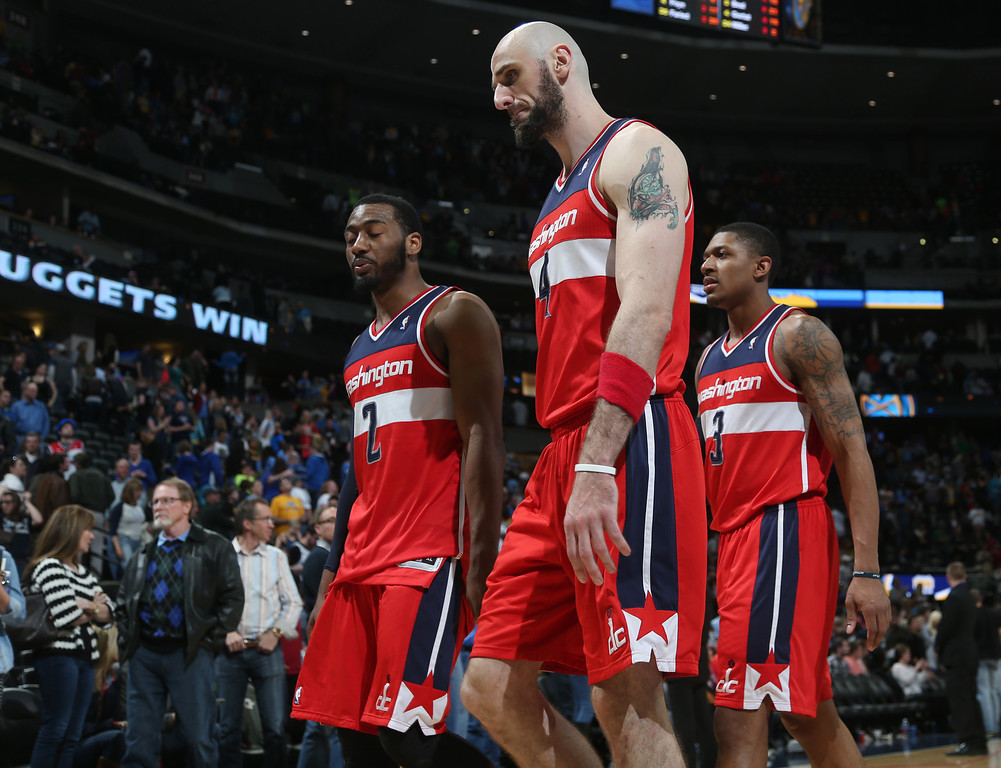 . From left, Washington Wizards guard John Wall, center Marcin Gortat, of Poland, and guard Bradley Beal head to the locker room after the Denver Nuggets\' 105-102 victory over the Wizards in an NBA basketball game in Denver on Sunday, March 23, 2014. (AP Photo/David Zalubowski)