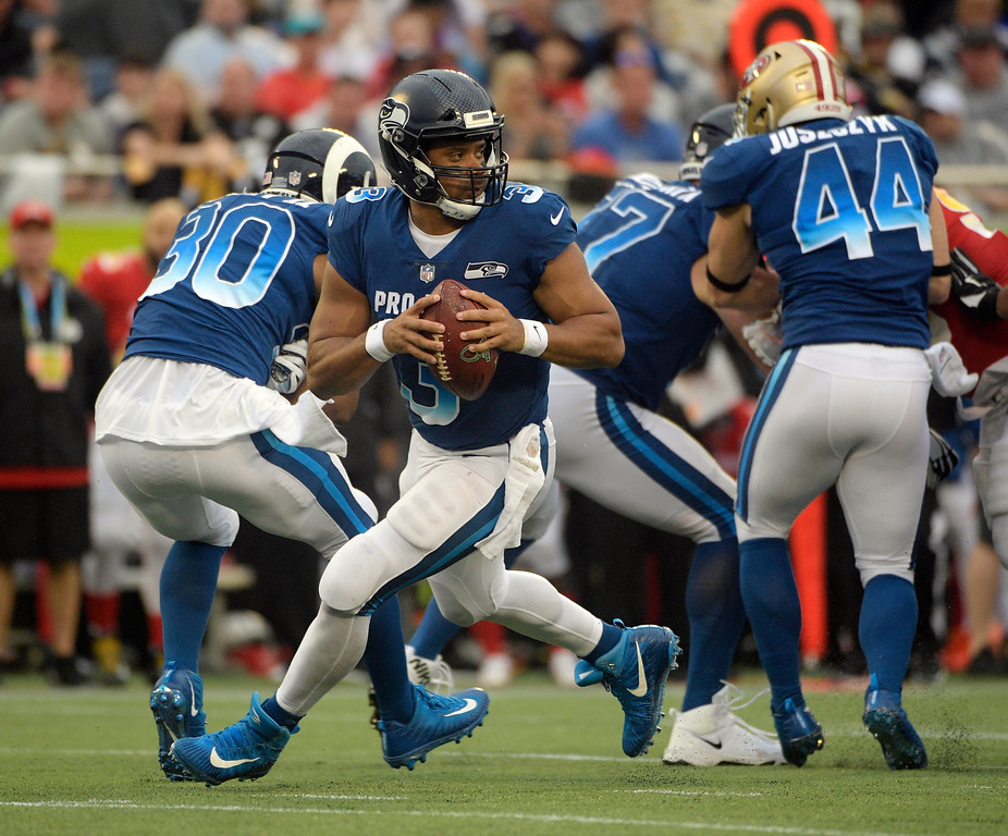 . NFC quarterback Russell Wilson of the Seattle Seahawks, looks to pass, during the second half of the NFL Pro Bowl football game against the AFC, Sunday, Jan. 28, 2018, in Orlando, Fla. (AP Photo/Phelan M Ebenhack)