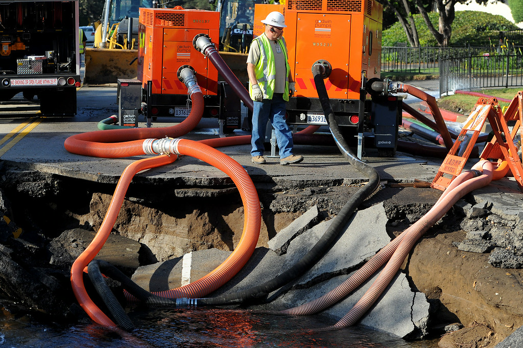 . Water is pumped from a sinkhole from the broken water main on Sunset Boulevard near UCLA, Wednesday, July 30, 2014. (Photo by Michael Owen Baker/Los Angeles Daily News)