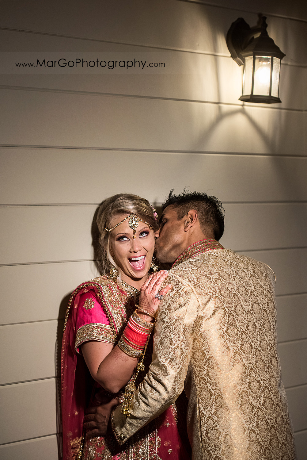 Indian groom kissing the bride's cheeck at Elliston Vineyards in Sunol