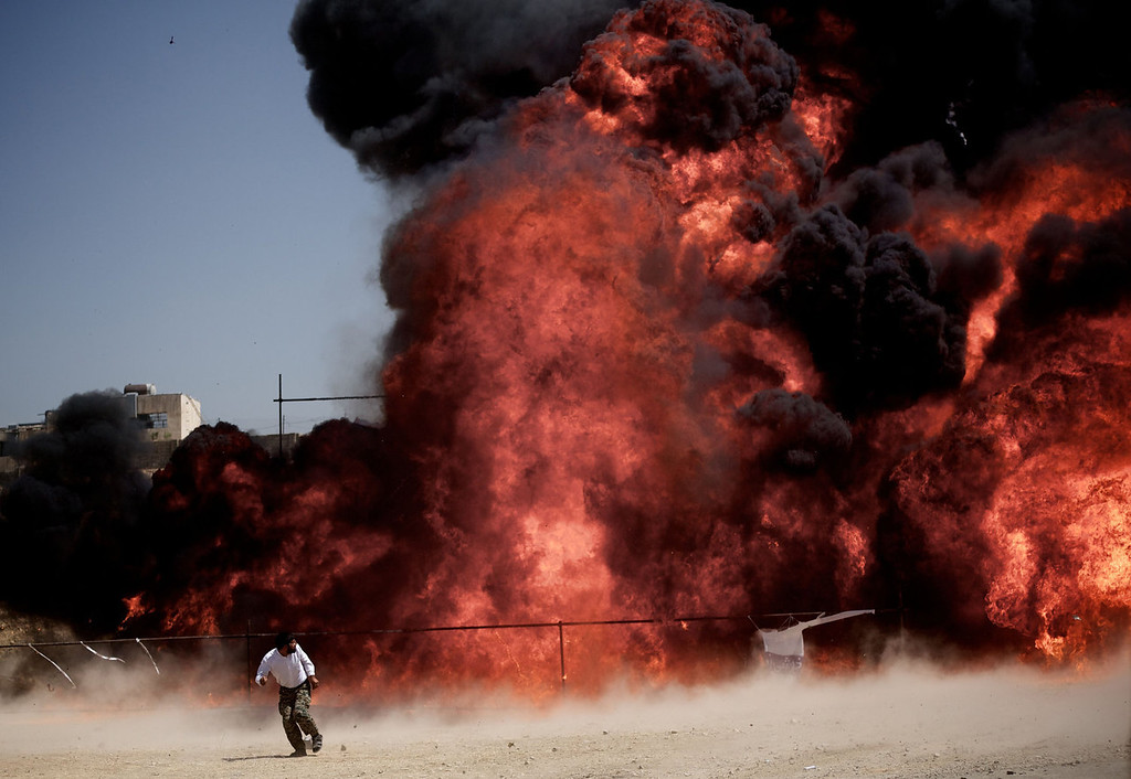 . An Iranian man who was fixing explosives wires run away after setting ablaze 50 tons of drugs seized in recent months in eastern Tehran on June 26, 2013 to mark the International Day Against Drug Abuse and Illicit Trafficking.   BEHROUZ MEHRI/AFP/Getty Images