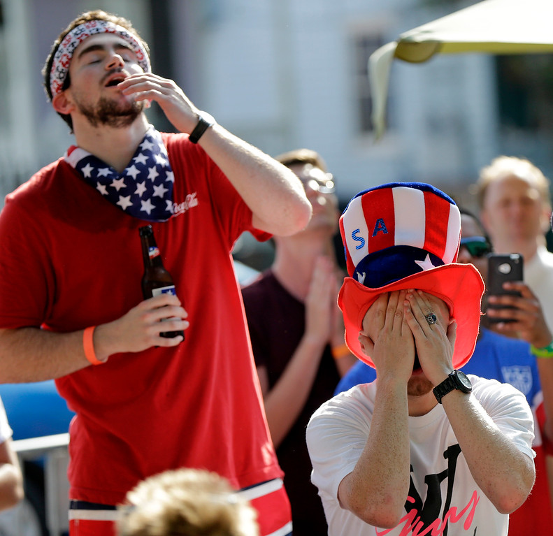 . USA soccer fans John Anderson, right, and Eric Carmedelle, both of New Orleans, react during the U.S. soccer team loss to Belgium at a viewing site outside Finn McCool\'s Irish Pub in New Orleans, Tuesday, July 1, 2014. The U.S. lost 2-1 in extra time. (AP Photo/Gerald Herbert)