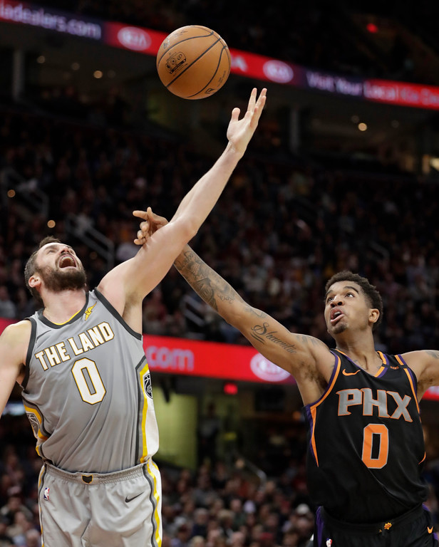 . Cleveland Cavaliers\' Kevin Love, left, and Phoenix Suns\' Marquese Chriss reach for a rebound in the first half of an NBA basketball game Friday, March 23, 2018, in Cleveland. (AP Photo/Tony Dejak)