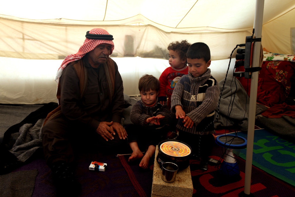 Description of . Syrian refugee family warm themselves inside their tent , at Zaatari Syrian refugee camp, near the Syrian border in Mafraq, Jordan, Tuesday, Jan. 8, 2013. Syrian refugees in a Jordanian camp attacked aid workers with sticks and stones on Tuesday, frustrated after cold, howling winds swept away their tents and torrential rains flooded muddy streets overnight. Police said seven aid workers were injured. (AP Photo/Mohammad Hannon)