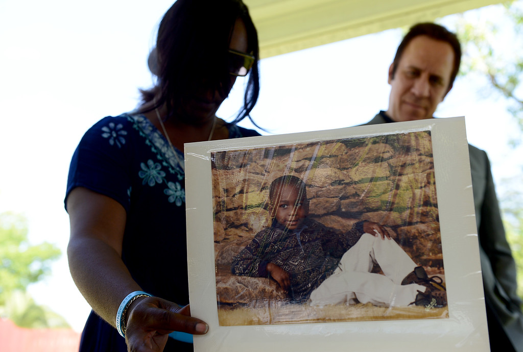 . With support of her attorney Dale Galipo, Anya Slaughter shows scrap books of her son Kendrec McDade as friends and family observe what would have been his 21st birthday at Northside Park in Azusa, Saturday, May 11, 2013. McDade, who was shot and killed by Pasadena police officers who claimed he was �reaching for his waistband� and was unarmed, would have turned 21 on May 5, 2013. March 24 will mark the year anniversary of his death. (SGVN/Staff Photo by Sarah Reingewirtz)