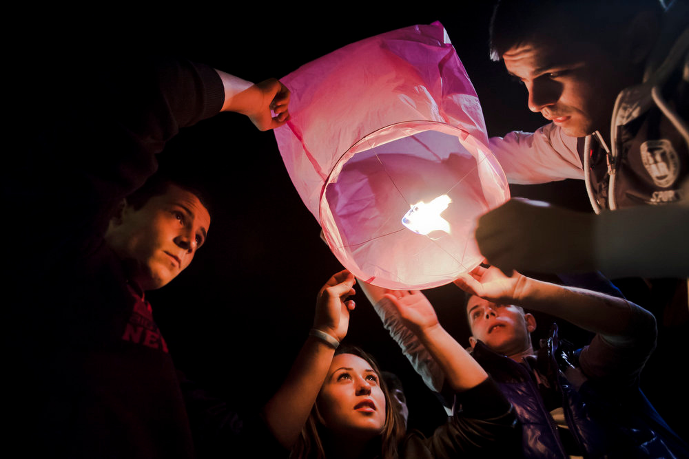 . Youngsters light up a lantern during the orthodox Easter religious service in the Black Sea port of Mangalia, Romania, Sunday, May 5, 2013. Up to 7.000 people attended the service and 5.000 lampoons were launched, according to local media.   (AP Photo/Bogdan Chesaru)