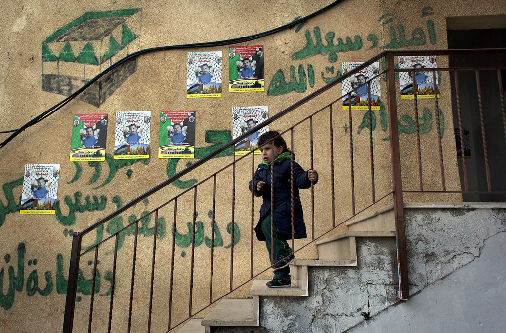 ". A child walks down the stairs of the family home of Ahmed Shehadeh, one of 26 Palestinian prisoners expected to be released later tonight, next to posters with his picture and Arabic that reads ""welcome,\"" in the Qalandia refugee camp at the outskirts of the West Bank city of Ramallah, Monday, Dec. 30, 2013. Israel and the Palestinians are gearing up for the expected release by Israel of 26 of the longest-serving Palestinian prisoners, who were all convicted in deadly attacks of Israelis, as part of a U.S.-brokered package to restart peace talks. (AP Photo/Nasser Nasser)"
