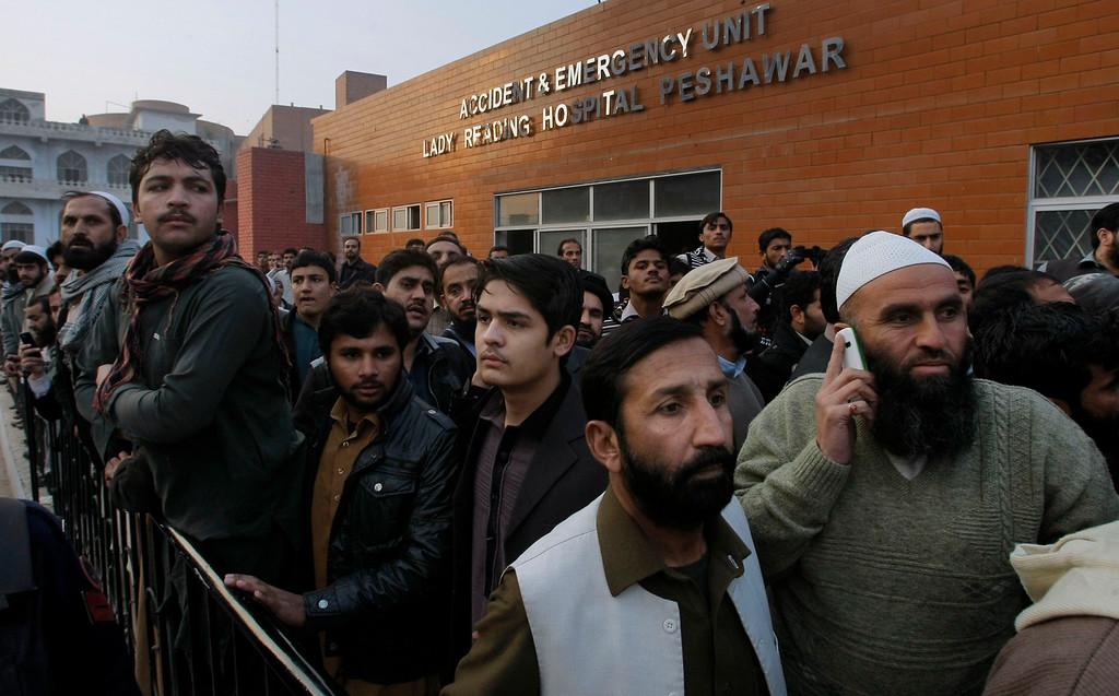 . People gather at a hospital, where victims of a Taliban attack are being treated in Peshawar, Pakistan, Tuesday, Dec. 16, 2014. Taliban gunmen stormed a military-run school in the northwestern Pakistani city of Peshawar on Tuesday, killing more than a hundred people, officials said, in the highest-profile militant attack to hit the troubled region in months. (AP Photo/Mohammad Sajjad)