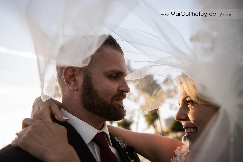 bride and groom under veil at San Diego Marina Village