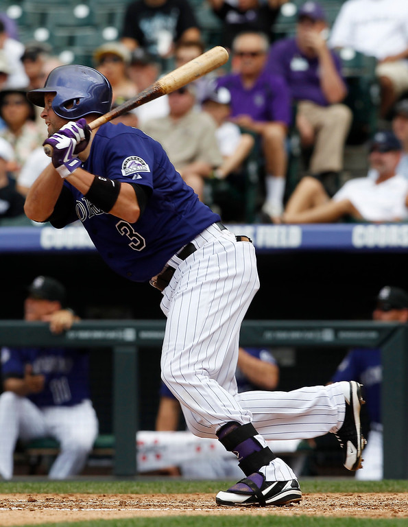 . Colorado Rockies\' Michael Cuddyer follows the flight of his RBI-double against the Washington Nationals in the fourth inning of a baseball game in Denver, Thursday, June 13, 2013. (AP Photo/David Zalubowski)