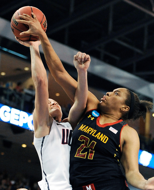 . Maryland\'s Tianna Hawkins (21) stops a shot attempt by Connecticut\'s Kelly Faris during the first half of a regional semifinal in the NCAA college basketball tournament in Bridgeport, Conn., Saturday, March 30, 2013. (AP Photo/Jessica Hill)