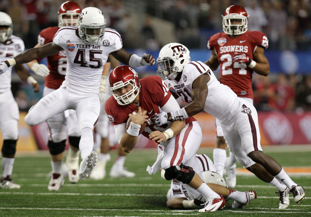 . Oklahoma\'s Blake Bell (10) is chased down after a long run by Texas A&M\'s Steven Terrell, right, and Jonathan Stewart, bottom, as Steven Jenkins (45) watches in the first half of the Cotton Bowl NCAA college football game Friday, Jan. 4, 2013, in Arlington, Texas. (AP Photo/LM Otero)
