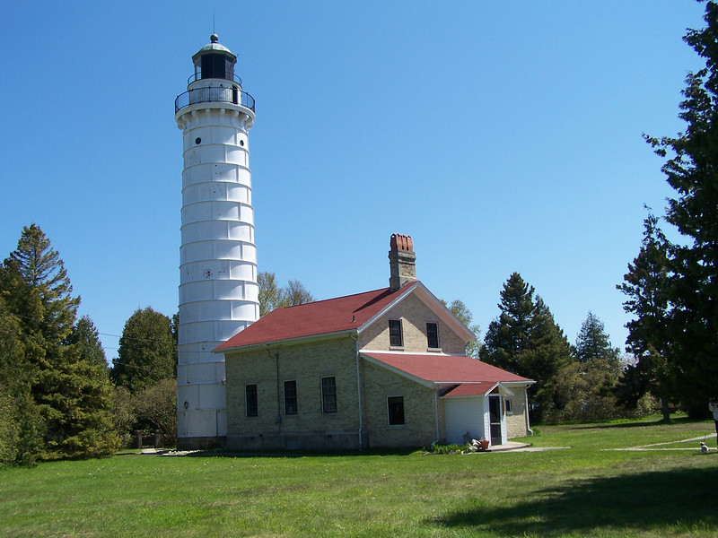 "Cana Island Lighthouse, Baileys Harbor, WI.  Construction of the cream city brick building and 65' tower was begun in 1869. Because of its location, Cana Island is vulnerable to severe storms, and in 1902 the exterior of the tower was encased in steel and painted white.  The Third Order Fresnel lens still shines to warn vessels.  The Door County Maritime Museum leased the property in the 1970's to preserve it for the public. Access to the ""island"" is by crossing the rocks from the mainland."