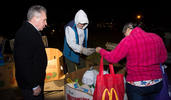 11/25/19 Wesley Bunnell | StaffrrThanksgiving meals were distributed by HRA workers and volunteers on Monday evening at their Osgood Park location. Lawrence Varholak, L, part of a group of volunteers from Hexcel Corporation, along with HRA employee Bob Garey help a client pick out a frozen turkey.