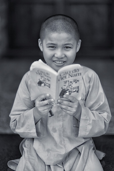 Boy Monk reading a book in Vietnamese