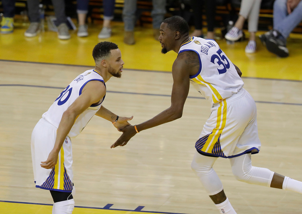 . Golden State Warriors guard Stephen Curry, left, celebrates with forward Kevin Durant (35) during the first half of Game 1 of basketball\'s NBA Finals against the Cleveland Cavaliers in Oakland, Calif., Thursday, June 1, 2017. (AP Photo/Marcio Jose Sanchez)